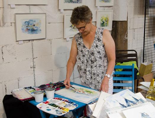Martine SAINT ELLIER peint devant les visiteurs aux  Ateliers Ouverts des Rosiers-sur-Loire
