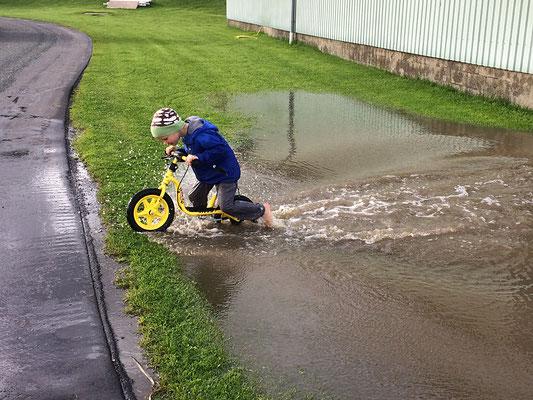 Kind auf einem Laufrad fährt durch eine tiefe Pfütze
