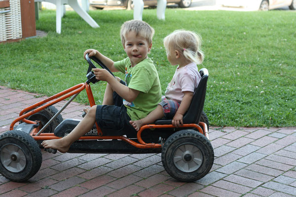 Zwei Kinder auf kleinem Kettcar
