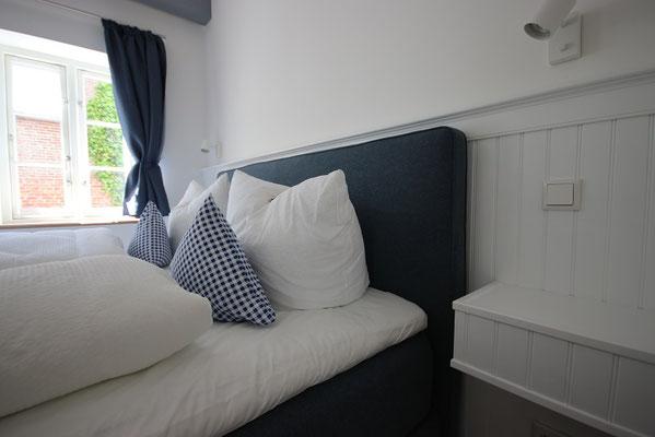Schlafzimmer mit Box-Spring-Bett in der Ferienwohnung Schäfer's Loge und edler Vertäfelung aus Beadboard