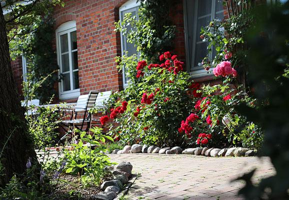 Romantische Sitzecke mit weißen Holz-Gartenmöbeln und roten Rosen