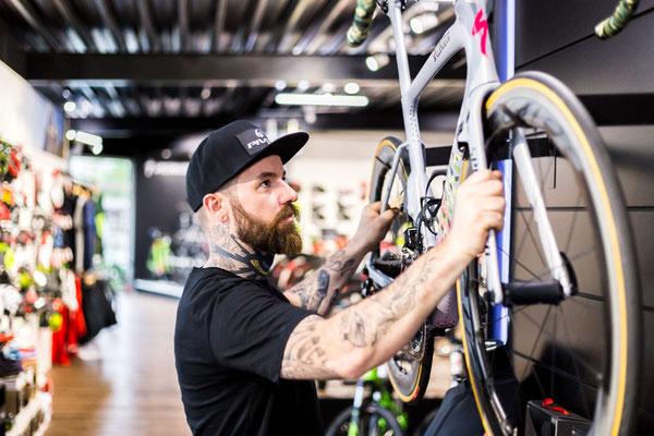 Inhaber des Fahrradladens hängt ein teueres Rennrad im Verkaufsraum auf.