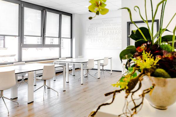 Ansicht eines hellen modernen Büros mit großen Fenstern wird von Sonnenstrahlen geflutet.