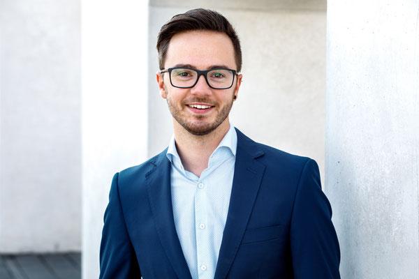 Bewerbungsfoto eines jungen Manns mit Brille und blauem Anzug vor einem Beton