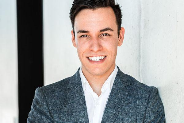 Bewerbungsfoto eines jungen Manns im grauen Anzug mit weißem Hemd und einem strahlenden Lächeln vor einer Betonwand.