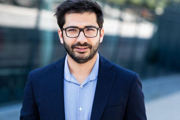 Bewerbungsfoto eines jungen Mannes mit Brille im dunkelblauen Anzug ohne Krawatte vor einer Gebäudefassade