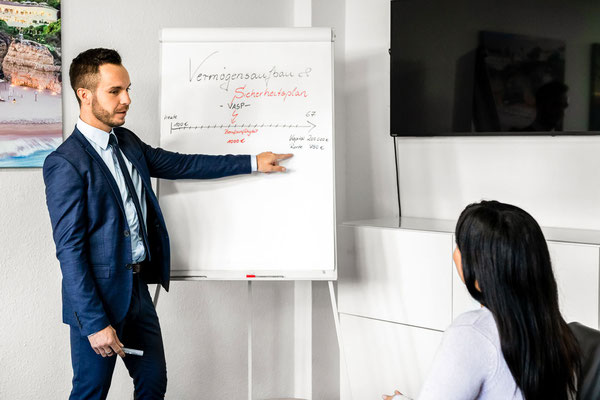 Ein Mann im Businessoutfit coached eine junge Frau in Finanzsachen