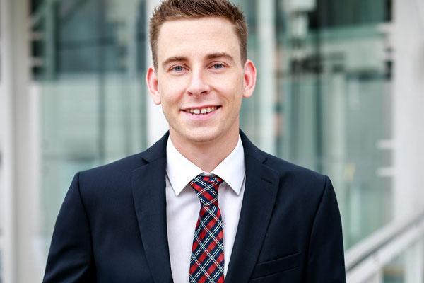 Bewerbungsfoto eines jungen Mannes im Anzug mit karierter Krawatte  vor Gebäudefassade