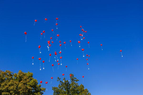 Rote Herzchen-Ballons steigen zur Hochzeitsfeier in den blauen Himmel.
