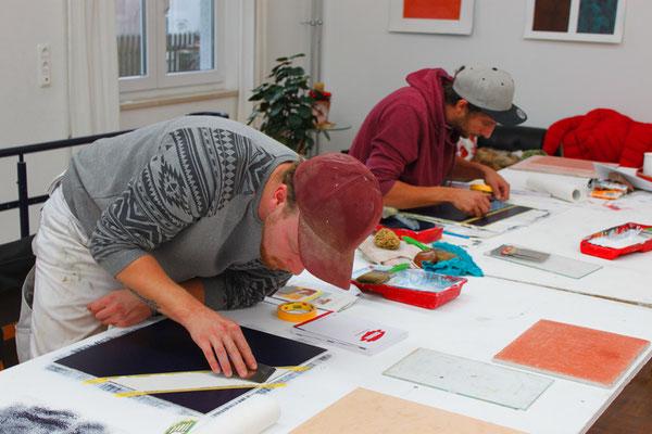 Teilnehmer aus dem Seminar üben eine Spachteltechnik auf Musterplatten