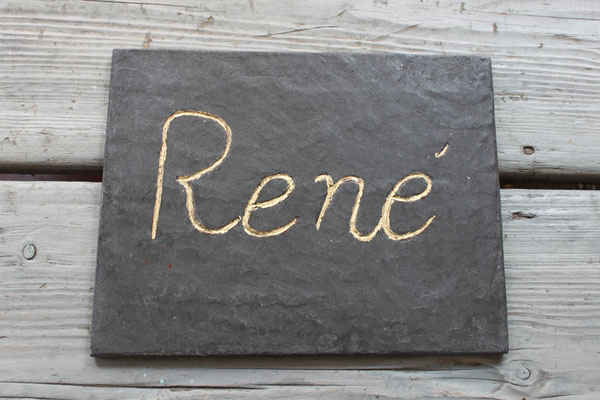 Sgrafitto in grauer Kalkglätte mit vergoldeten Schriftzug