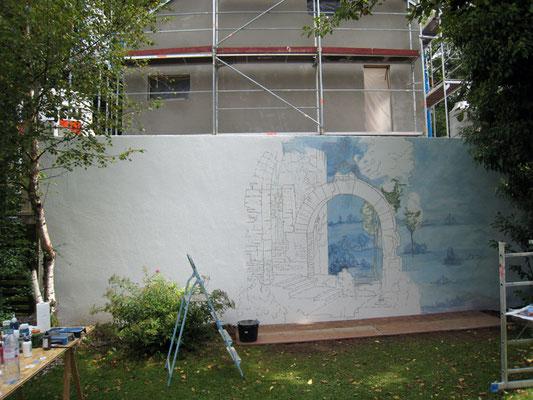 Die bemalte Gartenmauer soll den Gartenraum öffnen und eine gemütliche Atmosphäre in dem kleinen Garten schaffen.