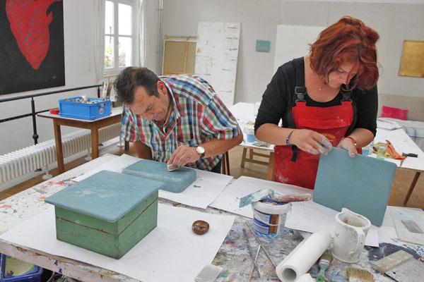 Zwei Kursteilnehmer arbeiten an ihren Musterplatten mit Tadelakt