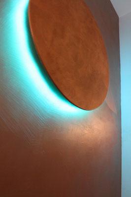 Goldlampe mit blauen Licht auf einer Goldwand