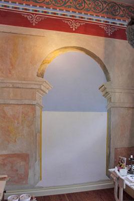 Ein gemalter Torbogen an einer Wand öffnet den Raum und lässt ihn dadurch größer wirken