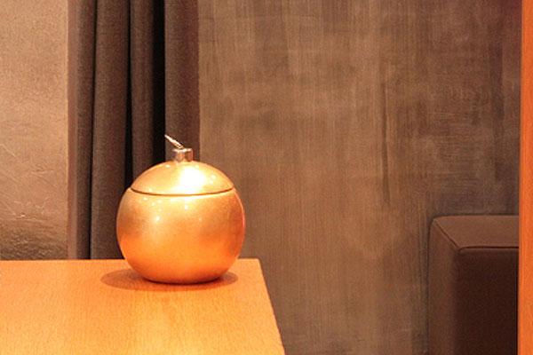 Vergoldetes Gefäß vor einer silber bemalten Wand