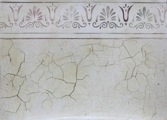 Griechisches Ornamnet als Sims über einer Wandfläche mit Craquéle