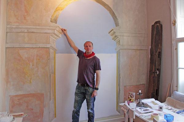 Der Wandmaler René Claus von Aufwind vor seinem Trompe l´oeil in München