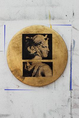 Eine runde Scheibe wurde vergoldet und mit einem Motiv versehen.