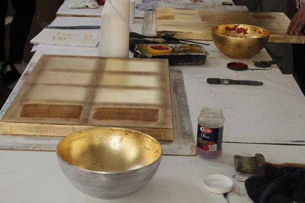 Das Anlegen des Schlagmetalls wird auf einem Holzpanel geübt. Das Ergebnis ist eine dekorative Goldtafel