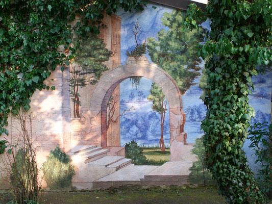 Die Illusionsmalerei an einer Gartenmauer in München integriert sich perkekt in den Außenraum