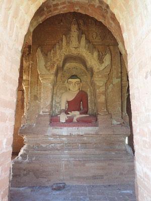 Bhumisparsha Mudra, die Geste der Erdberührung. Dabei hängt der Arm über das Knie und die Handflächen zeigen nach innen. Alle Finger weisen nach unten. Die linke Hand liegt mit der nach oben geöffneten Handfläche auf dem Schoss.