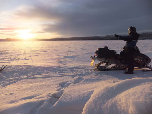 Schneemobiltour im Sonnenuntergang