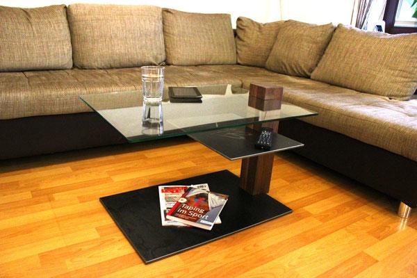 Wohnzimmertisch aus Nussbaum mit 360 Grad drehbarer VSG-Glasplatte und einer fest verbauten Ablagefläche aus Stahl im mittleren Bereich