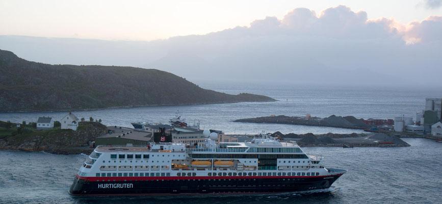 """Das Hurtigrutenschiff """"MIDNATSOL"""" fährt am 27.6.2018 um 11.28 Uhr im Hafen von Bodø ein. Ganz rechts scheint die Mitternachtssonne durch die Wolken."""