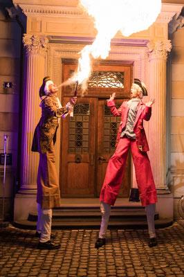 Stelzenläufer Künstler spucken Feuer an einer Feuershow