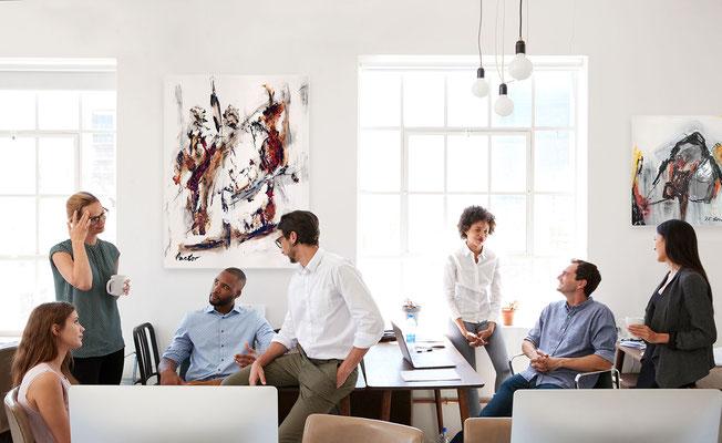 Motivierte Mitarbeiter bei einem Meeting. Büroausstattung mit Kunst für Ihr Unternehmen. Kunst mieten kaufen leasen.