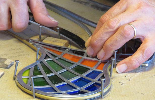 Kunstwerk Knochenbau, A. Linnenschmidt setzt Bleiruten und Farbgläser zusammen; © Foto Dr. P. Diziol