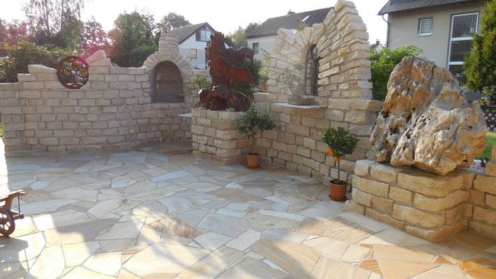 Sichtschutzmauer aus Naturstein mit integriertem Grill - Teakholzschnitzereien