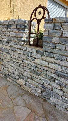 Sichtschutzmauer aus Naturstein mt gusseisernem Fenster