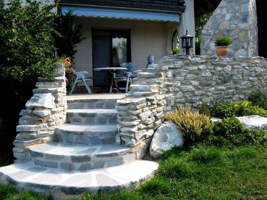 Steintreppenaufgang mit Natursteinmauer