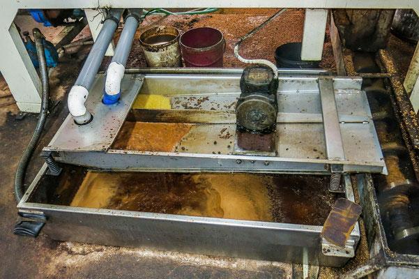 Öl und Schlacke werden getrennt. Das gelbe Öl wird nach oben geleitet. Die Schlacke fließt nach unten ab.