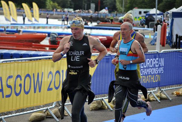 Philip Schädler hat die Schwimmstrecke absolviert und rennt in die Wechselzone