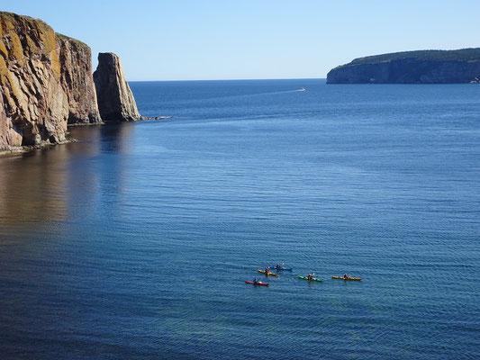 Urlaub in Quebec: Kanuten paddeln in ihren Kayaks vor dem Kalksteinfelsen Rocher Percé und der Bonaventure Insel.