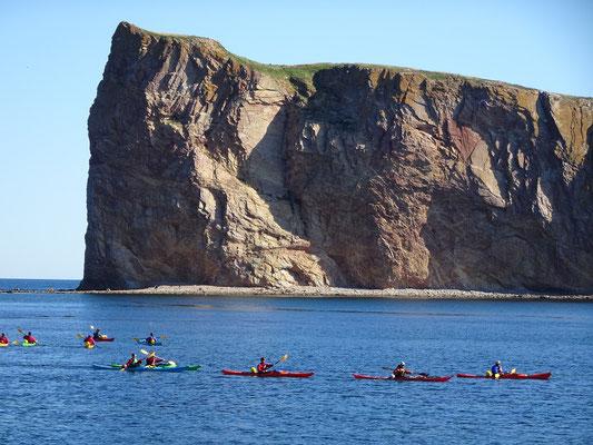 Urlaub in Quebec: Kanuten paddeln in ihren Kayaks vor dem Kalksteinfelsen Rocher Percé.