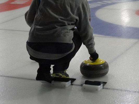 """Curling in Toronto: Startposition auf dem Block. Über den linken Schuh wurde eine extra glatte Sohle (""""Slider"""") gespannt, die praktisch null Reibung auf dem Eis verursacht."""