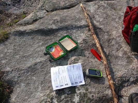 Der Cape Breton Highlands National Park hat seine eigene offizielle Geocaching-Challenge. Hier sieht man den Aufgabenzettel und die kleine rote Lochzange, dank der die Parkmitarbeiter wissen, ob man die Caches wirklich gefunden hat.