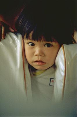 1982: auf der Fahrt mit dem Zug von Bangkok nach Chiang Mai beobachtet uns ein kleines Thai-Mädchen interessiert