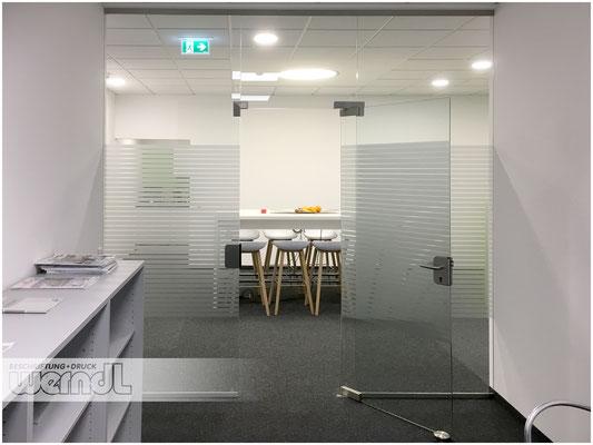Diskreter Sichtschutz im Büro mit einer partiellen Scheibenbeklebung mit Etched-Glass Streifen.