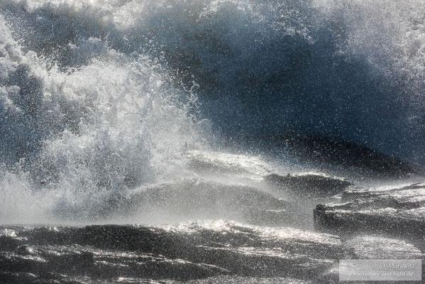 Wellen brechen sich an den Felsen der Küste