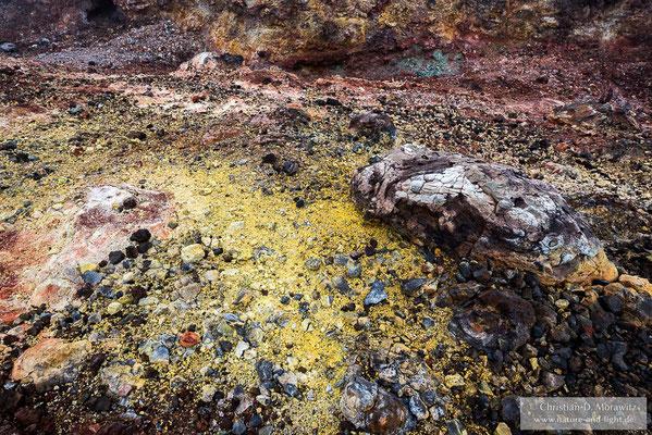 Durch Gasaustritte verfärbte Lava auf einem Schlackenkegel am Tolbatschik Vulkan