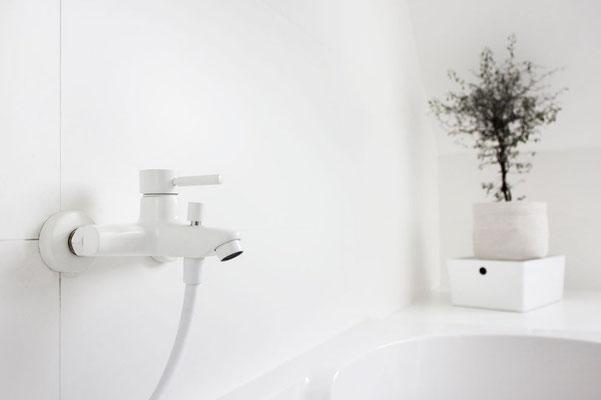 Weiße Badewannen-Armatur aus der Serie OXO mit Handbrause
