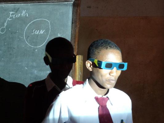 Mondfinsternis: Der hintere Schüler (Mond) wird von der Sonne (Beamerlicht von rechts) nicht angeleuchtet, da er sich im Erdschatten (vorderer Schüler) befindet.