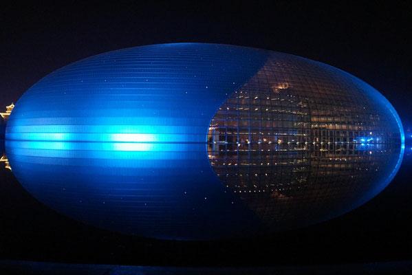 Das von Wasser umgebene Pekinger Nationaltheater bei Nacht.