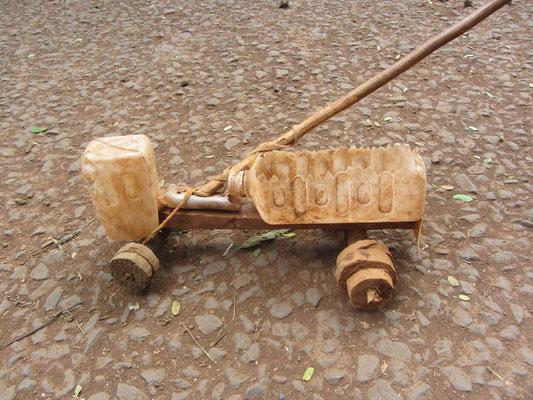Ein aus Zivilisationsabfall gebasteltes Auto eines tansanischen Jungens. Über die Drehung des Stockes wird der Einschlag der Vorderräder gesteuert!