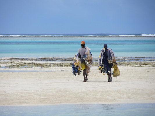 Sansibar: Zwei Fischer auf der Weg zur ihrer Arbeit im flachen Wasser der Ebbe.